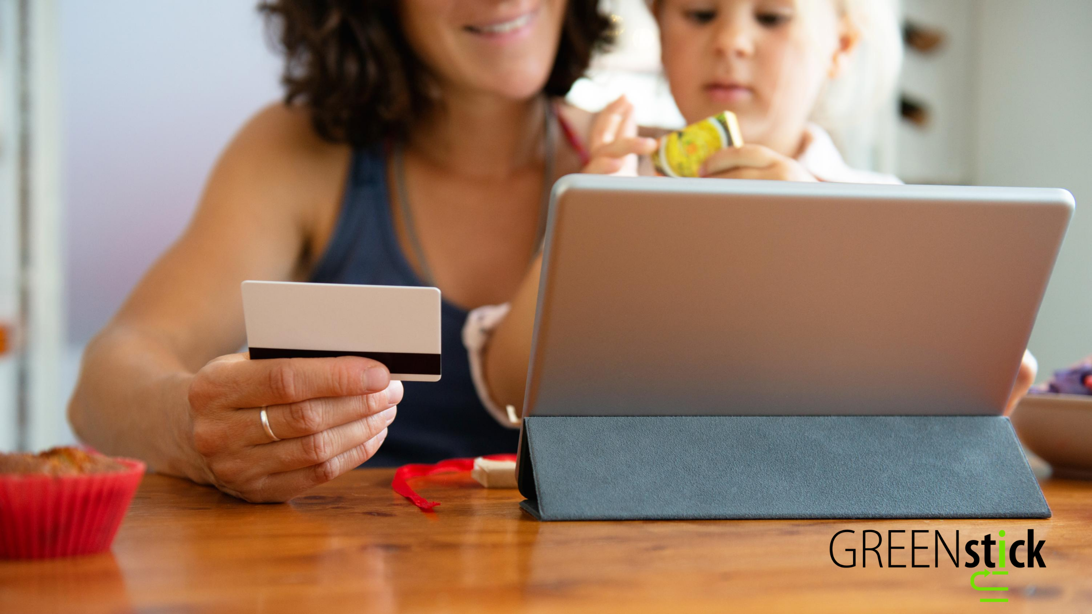 Adult women and baby girl shopping online on an ipad using a business gift card to complete their purchase.